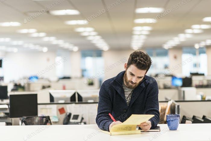 Ein Mann sitzt an einem Schreibtisch in einem Büro und schreibt mit einem roten Stift.