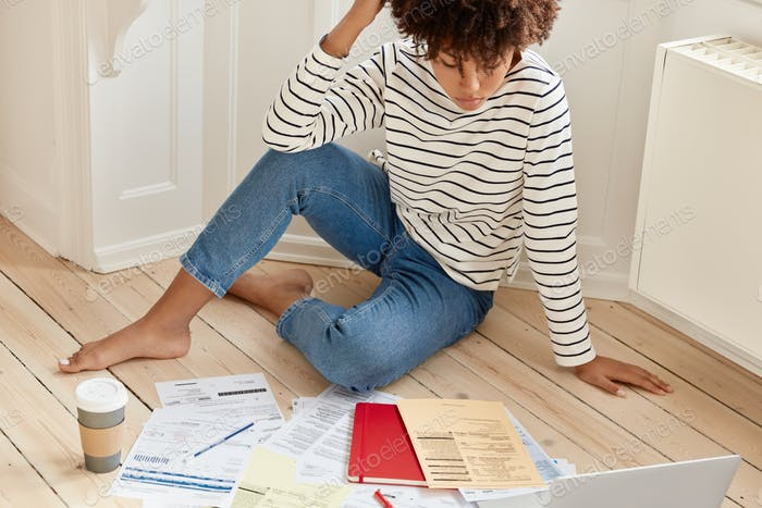 Relaxed freelancer dressed in striped sweater and jeans, works on investment contract, works overtim
