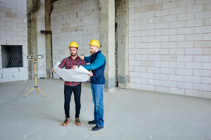 Two young builders in protective helmets discussing sketch in blueprint