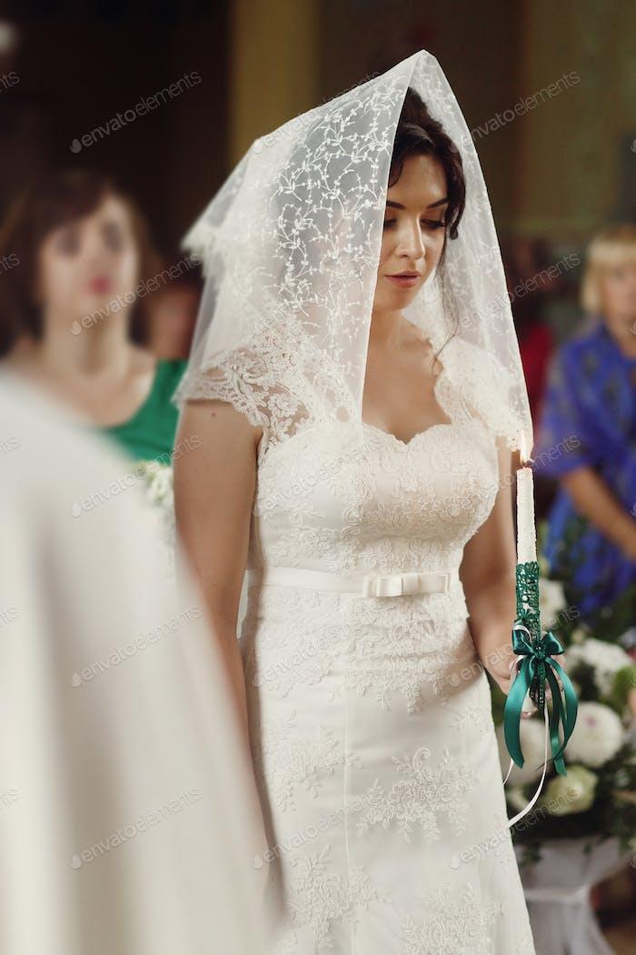 Beautiful brunette bride praying under veil in white wedding dress