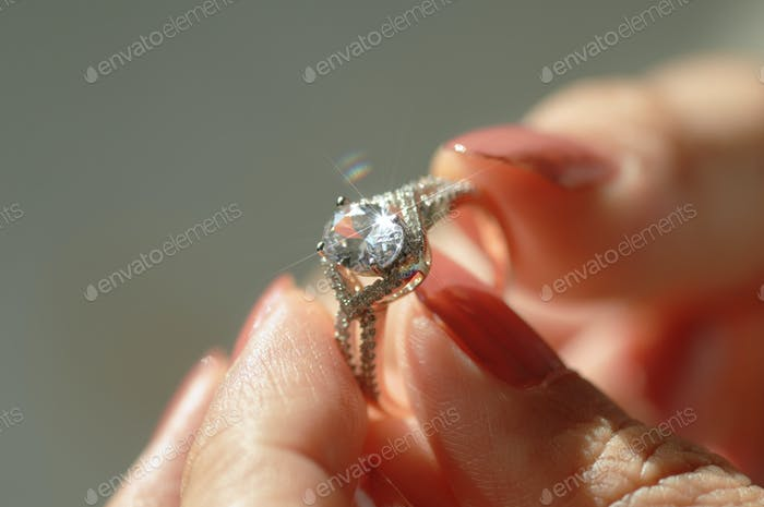 Close-up view of a diamond ring and woman hand