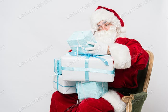 Photo of happy Santa Claus with giftboxes looking at them