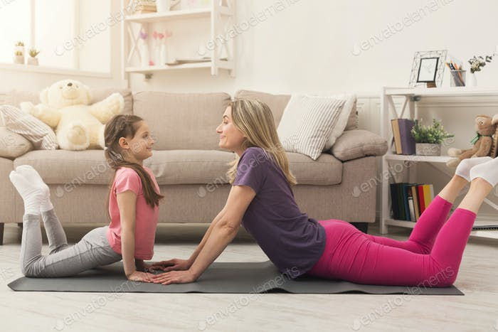 Young woman and child daughter doing yoga exercise at home