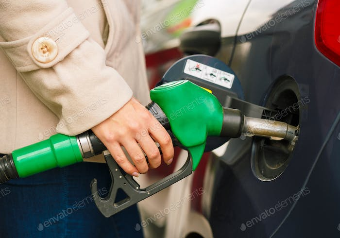 Woman fills petrol into her car at a gas station