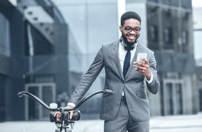 African-american businessman with smartphone standing with bike