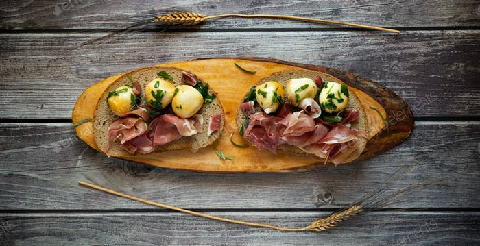 snack appetizer with wholemeal bread, raw ham and smoked provola