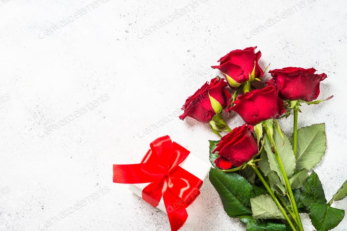Red roses flower and present box on white background top view.