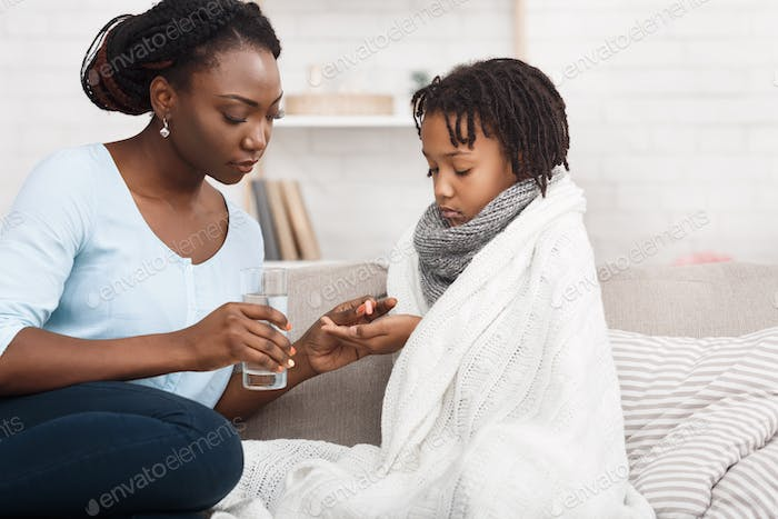 Black mum giving glass of water and pill