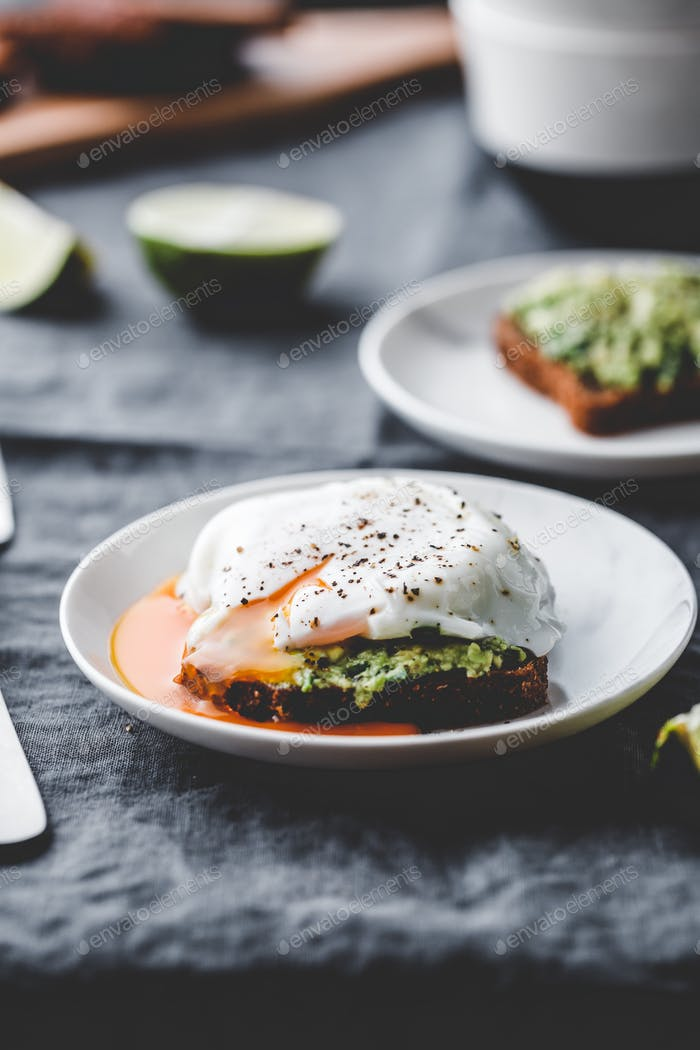 Avocado sandwich with rye bread and a poached egg.