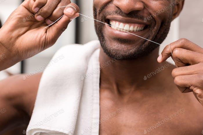 abgeschnittene Aufnahme eines jungen Mannes, der die Zähne mit Zahnseide putzt