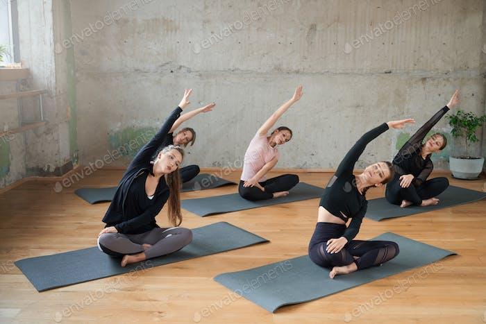 Gruppe von Frauen Stretching in Lotus-Pose in der Halle