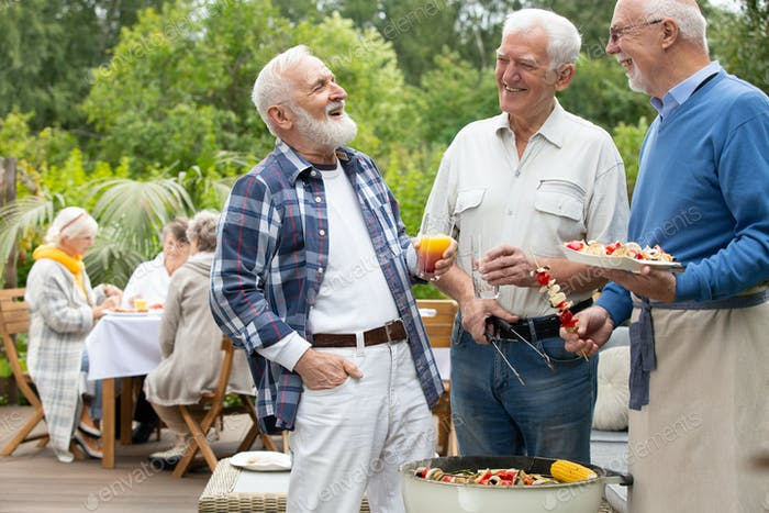 Senior friends with drinks and food standing next to grill during garden party