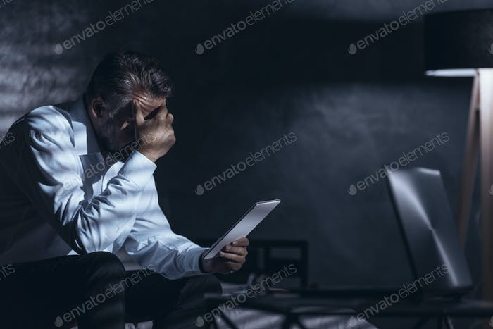 Tired businessman working at home