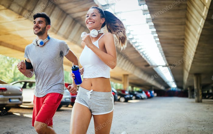 Athletic young and smiling couple jogging together