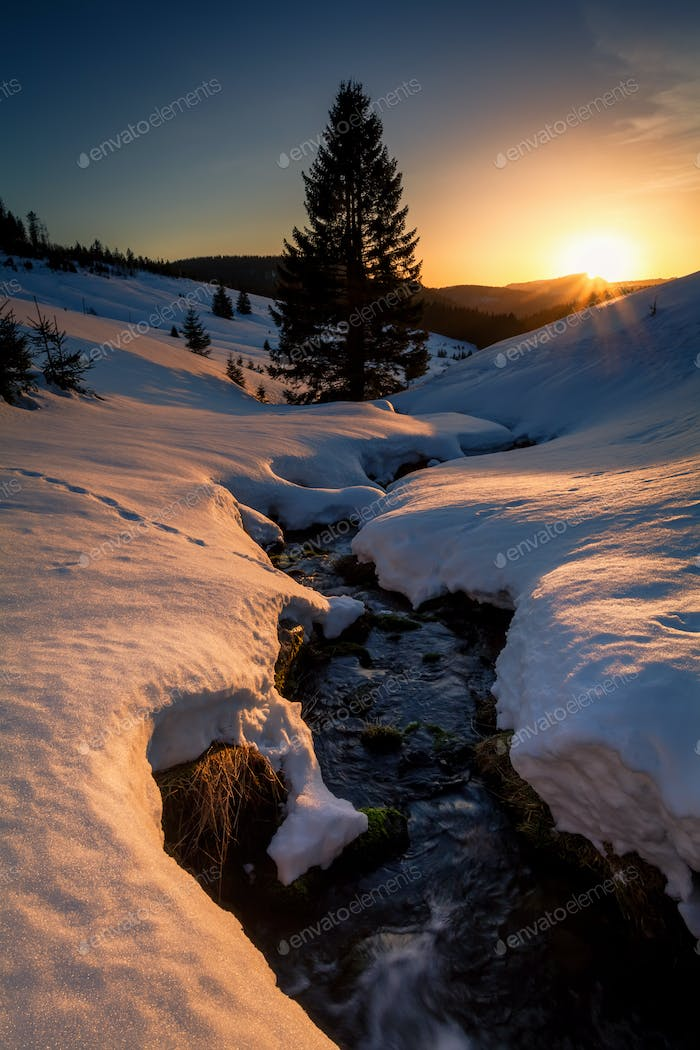 last sunrays over mountains river in winter