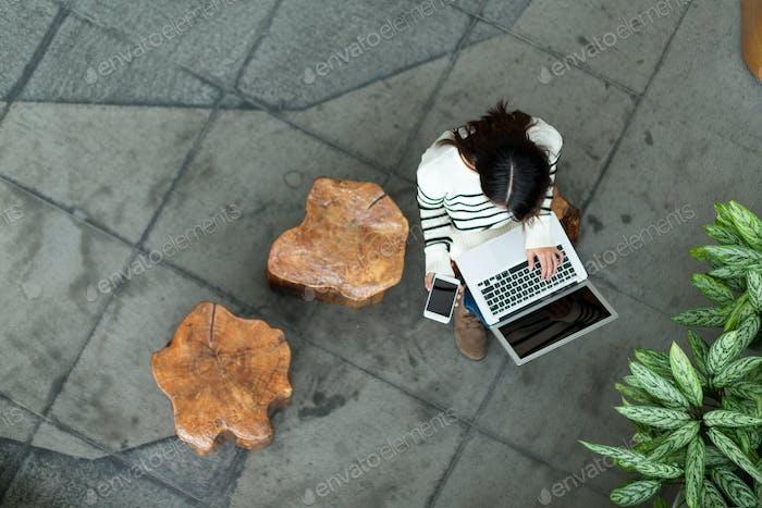 Draufsicht der Frauennutzung von Mobiltelefon und Laptop-Computer