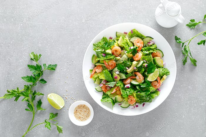 Shrimps salad with green lettuce, cucumbers and avocado, dressed with lime juice