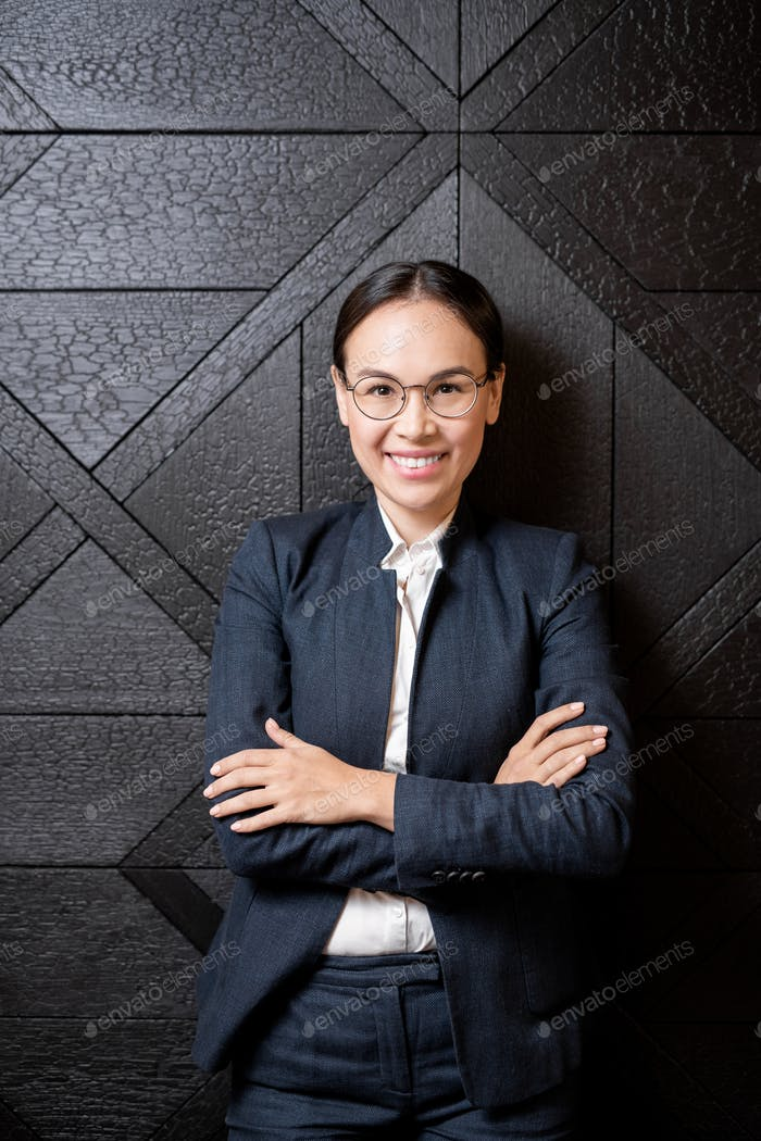 Young beautiful businesswoman with toothy smile crossing arms on chest