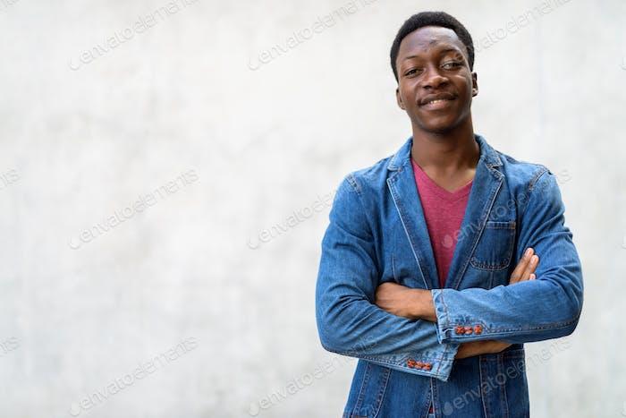 Junge gutaussehender afrikanischer Mann trägt Jeansjacke gegen Beton