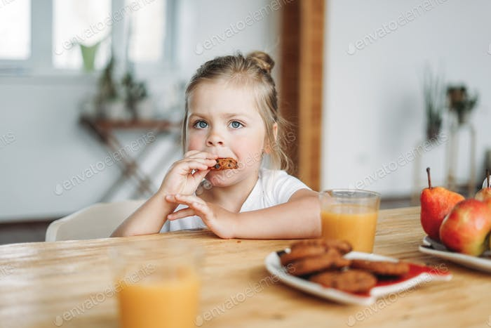 Cute toddler girl with fair hair and big grey eyes eat breakfast at table