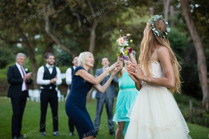 Rear view of bride holding flower bouquet