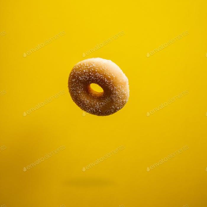 Sugar doughnut in motion falling on yelloy background