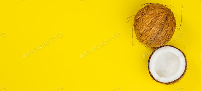 Coconuts on yellow background, top view