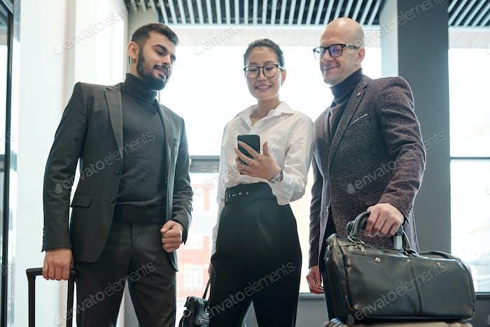Gruppe von reisenden Kollegen auf der Suche nach dem richtigen Weg zum Hotel im Netz
