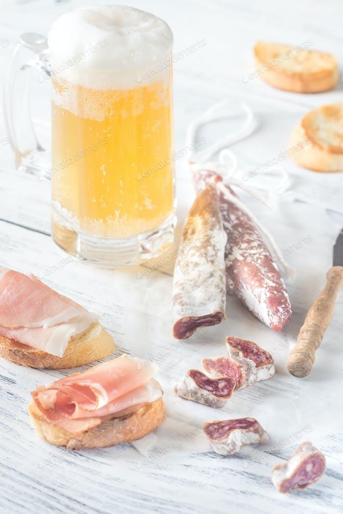 Mug of beer with sandwiches and smoked sausage