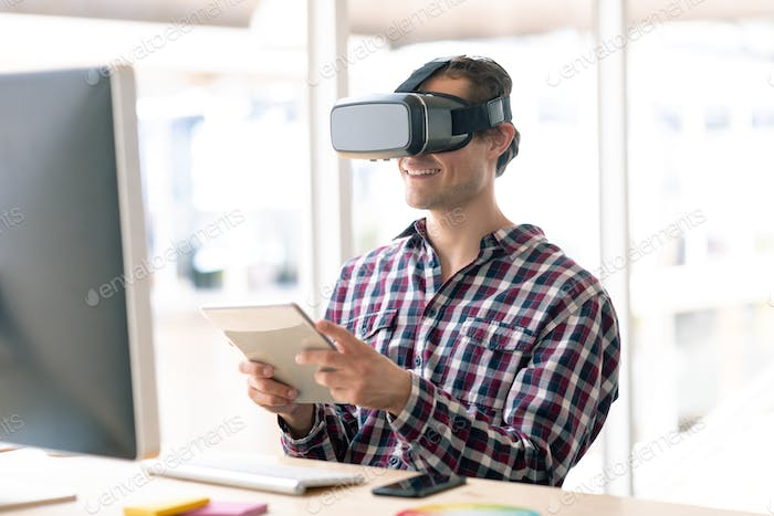 Caucasian male graphic designer using virtual reality headset while working on digital tablet