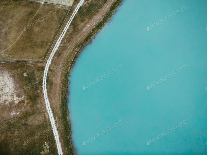 Top down aerial view over lake and rural road