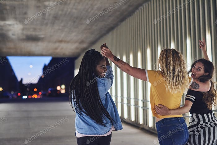Young friends holding hands and walking together in the city