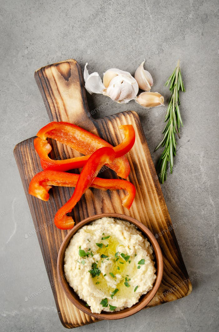 Hummus dip dish topped with chickpeas and olive oil served with red sweet bell pepper slices