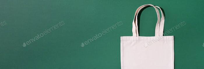Wiederverwendbare Textiltasche auf grünem Hintergrund. Zero-Waste Konzept mit Kopierraum. Zero Abfall, Kunststoff