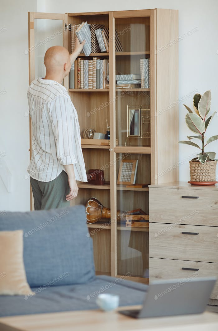 Bald Woman Putting Book in Bookcase at Home