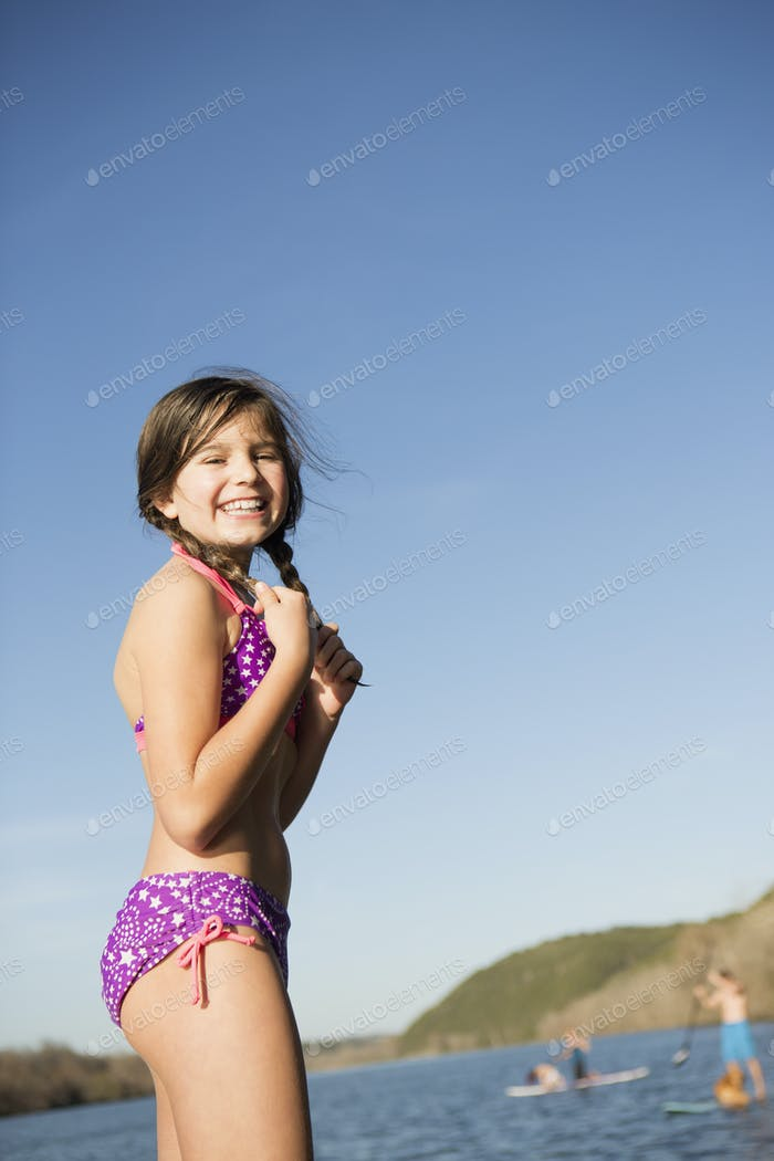 A young girl on a jetty with paddleboarders in the background.