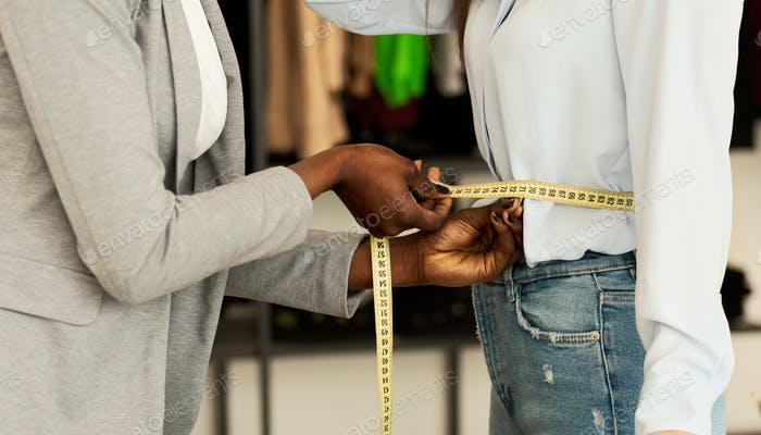African American Couturier Measuring Woman's Waist In Showroom, Cropped
