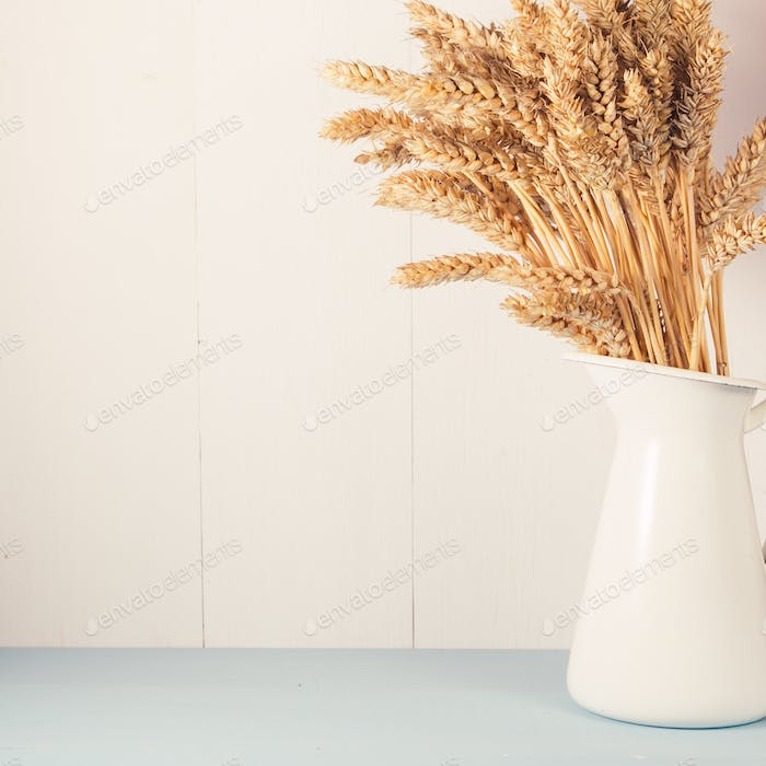 Ripe wheat in white vase on wooden background