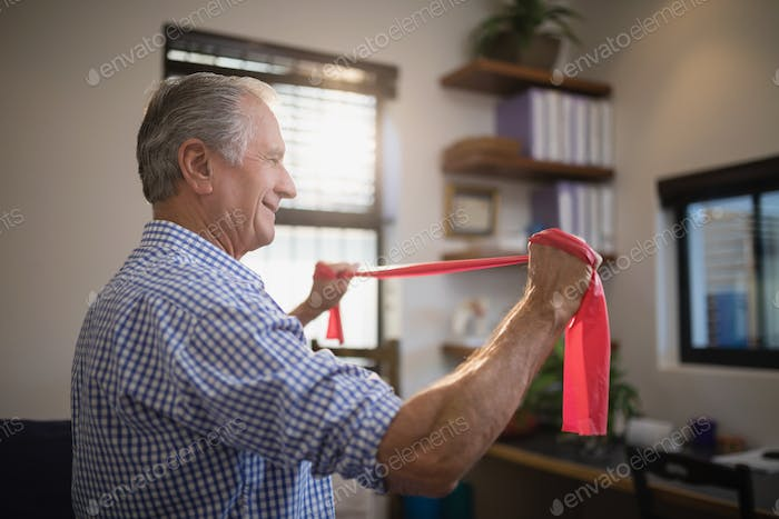 Side view of senior man pulling resistance band in hospital ward
