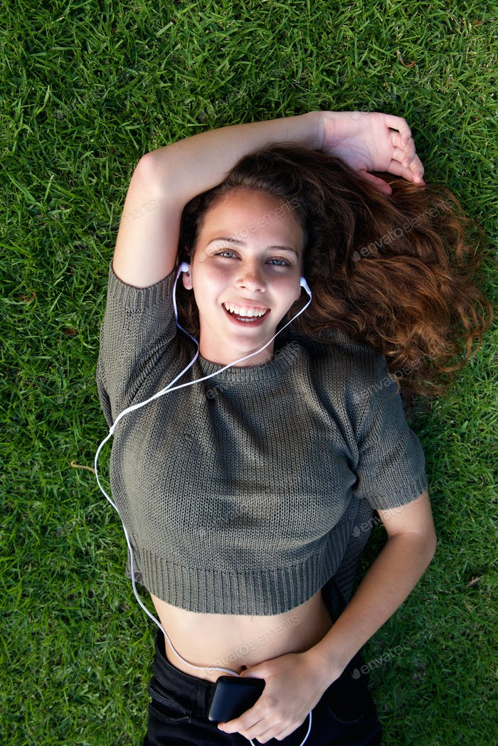 Laughing young woman lying on grass listening to music