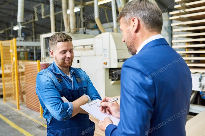 Senior Manager Talking to Worker at Factory