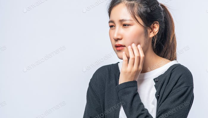 A woman sick with a toothache and a hand holding on the cheek