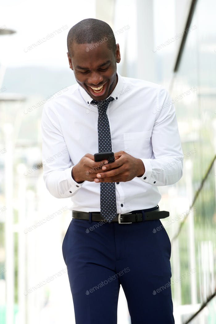 happy african american businessman walking and looking at cellphone on city street