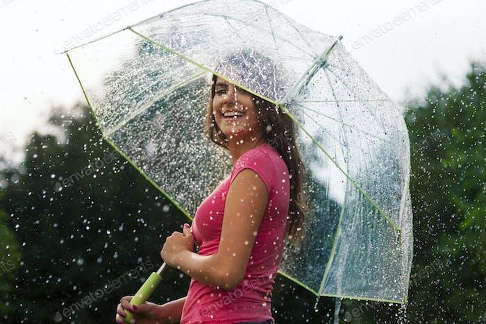 Mujer joven de pie en verano lluvia con paraguas