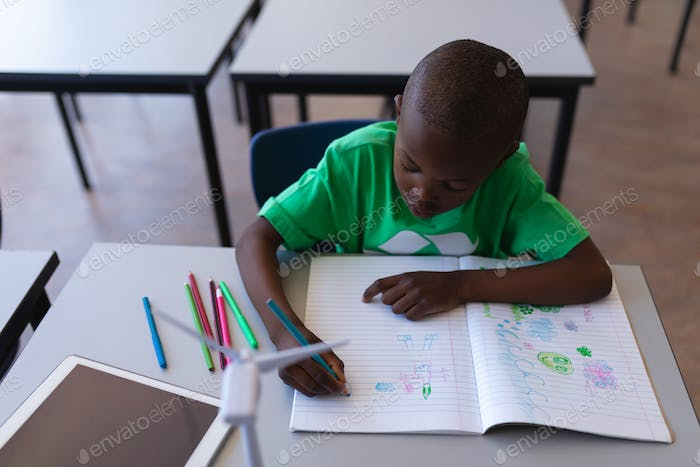 High angle view of schoolboy drawing on book at desk in classroom of elementary school