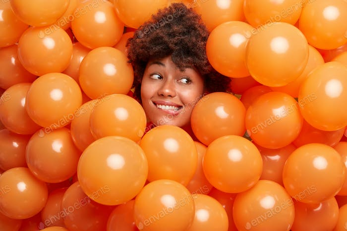 Photo of cheerful ethnic beautiful curly woman bites lips and looks cheerfully aside poses around in