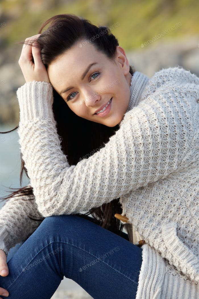 Smiling woman sitting outside in warm sweater