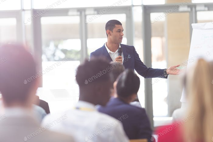Front view of handsome mixed-race businessman speaking in business seminar at conference