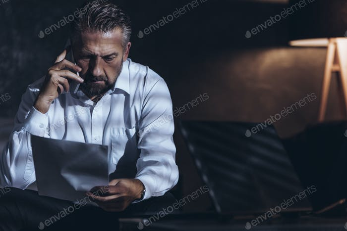 Stressed businessman using smartphone