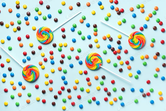 Multicolored lollipop, rainbow colorful candies on blue background. Coated chocolate sweet pieces